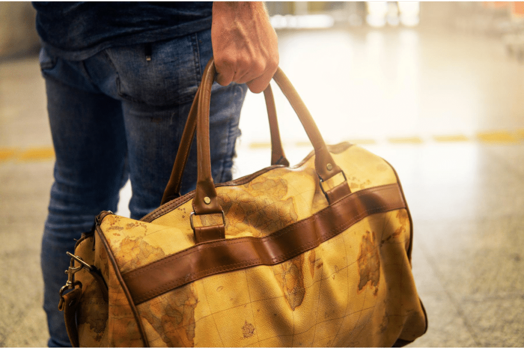 brown-colored leather duffel bag
