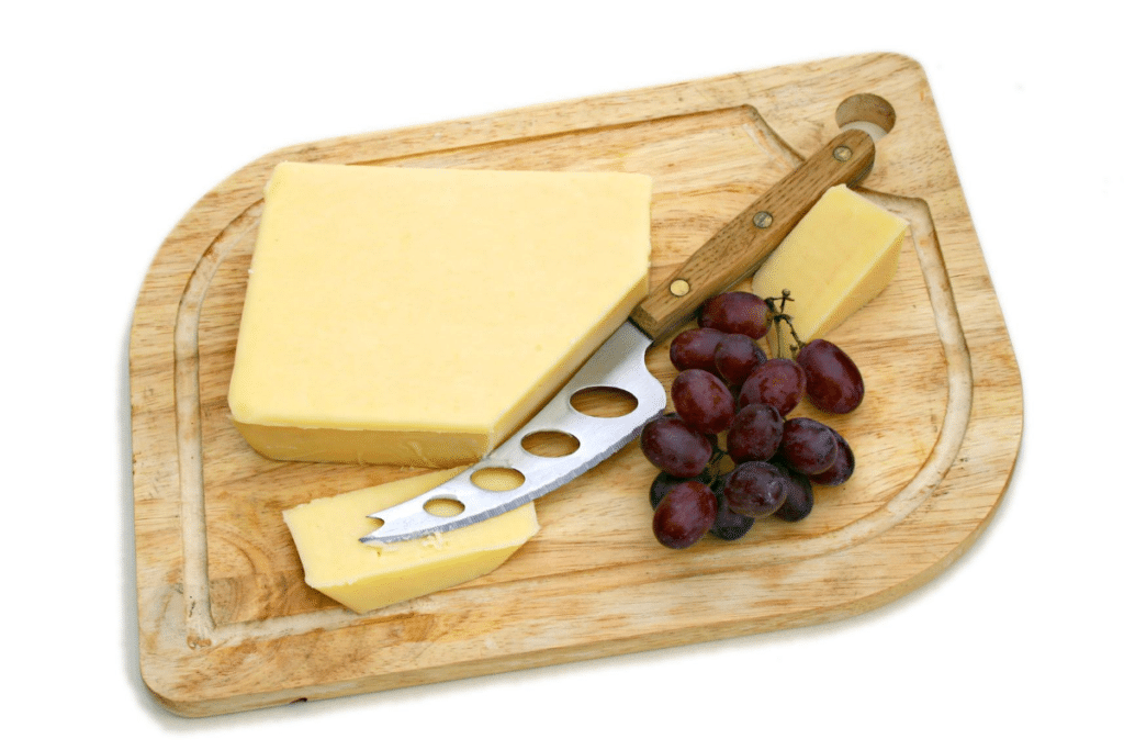 cheeseboard with knife, cheese and grapes
