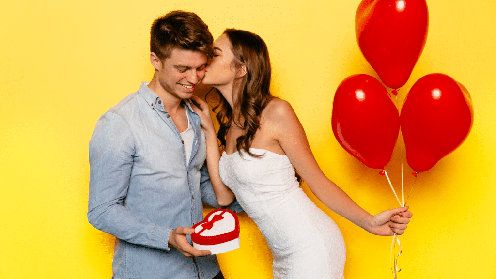 woman holding a red balloon while kissing a man with a heart-shaped box at hand