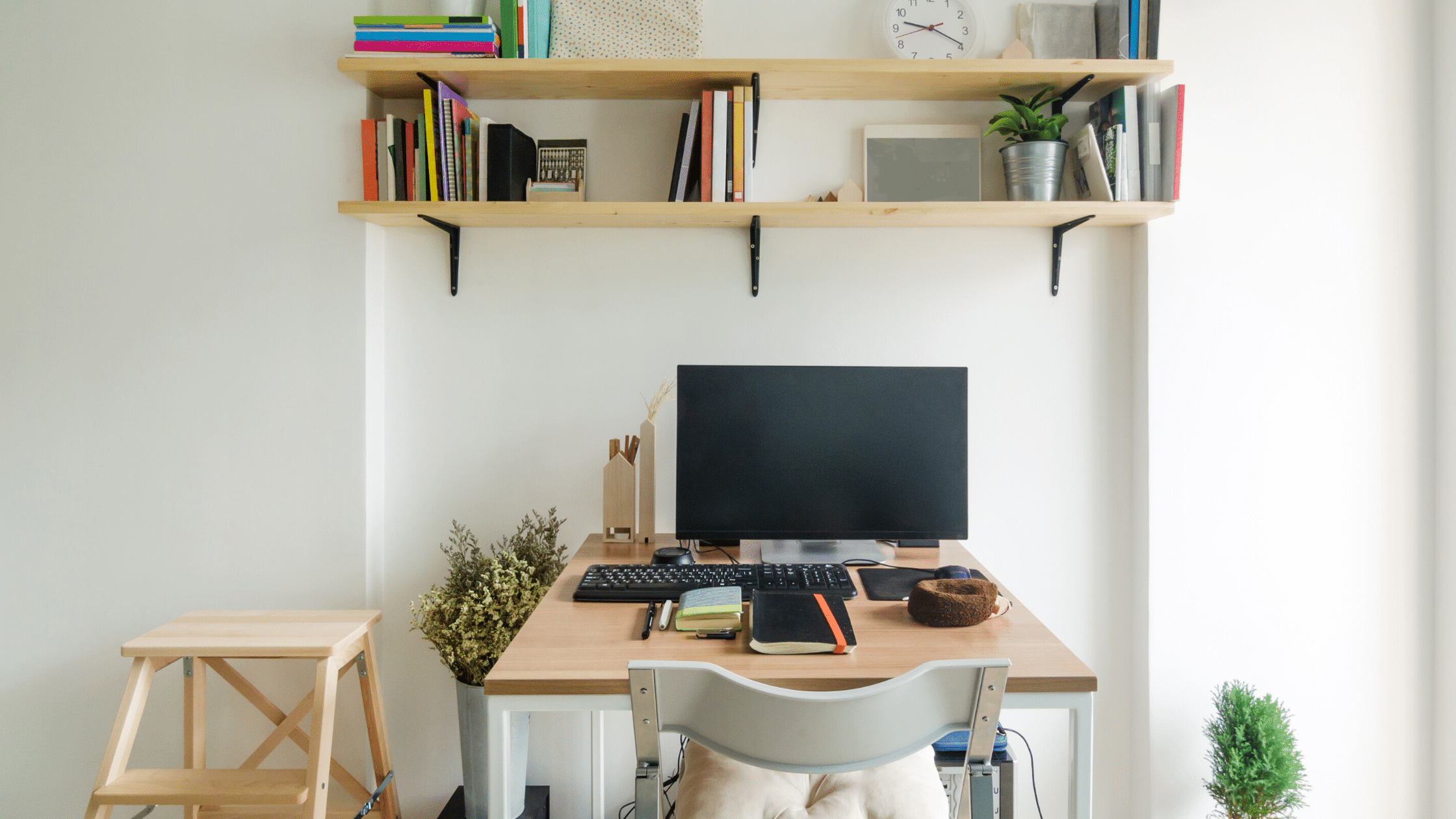 personal computer in a wooden table with indoor plants and notebooks